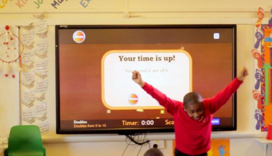 kid using touchscreen technology in classroom